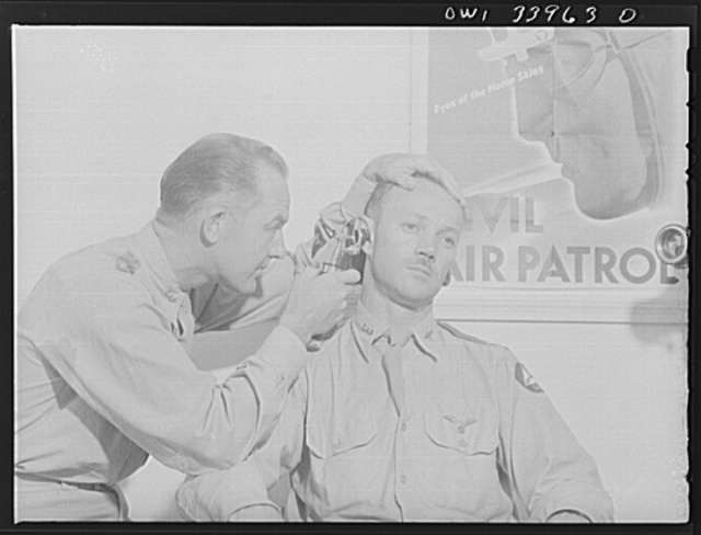 Corpus Christi, Texas. First Lieutenant R.V. Montague, a doctor from Okmulgee, Oklahoma and now a member of the Civil Air Patrol, giving an ear examination to Captain J.W. McLendon, former newspaper editor from Junction, Texas