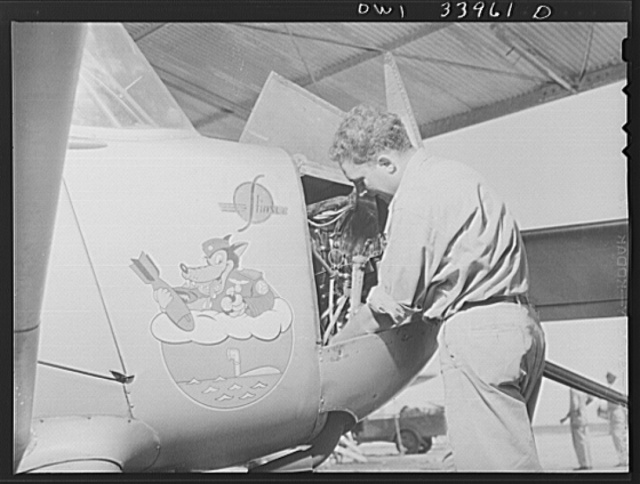 Corpus Christi, Texas. Seargent Hubert Green, member of the Civil Air Patrol, working on the motor of a plane of the Wolf Patrol