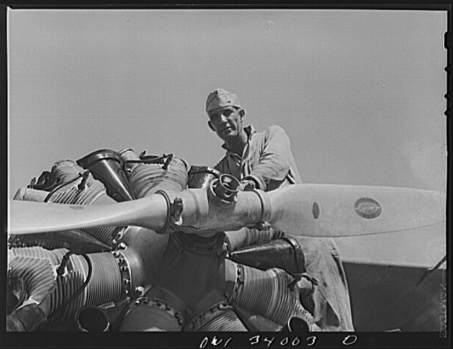 Corpus Christi, Texas. Sergeant George Caveres, a member of the Civil Air Patrol, working on the motor of a plane. Sergeant Caveres formerly operated a garage in Corpus Christi