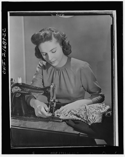Cynthia stiches basic seams before fitting, a principle of simplified sewing. While no new sewing machines are being made and the factories are turning out war goods (WPB (War Production Board) assures an adequate supply of machine repair parts for home dressmakers. To fully utilize existing machines, many women form communiuty pools, make machines available to those who would like to buy them and can't