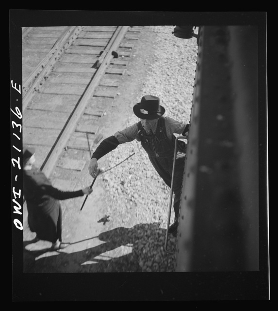 Dalies, New Mexico. Conductor C.W. Tevis picking up a message from a woman operator on the Atchison, Topeka and Santa Fe Railroad between Belen and Gallup, New Mexico
