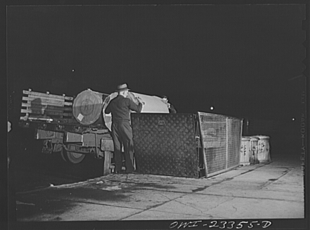 Dallas, Texas. Truck unloading rolls of Southland newsprint onto an elevator to the basement of the Dallas Morning News