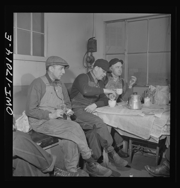 Daniel Senise at lunch in the work shanty at an Indiana Harbor Belt Line railroad yard. With him are (left) switchman John McCarthy and (right) switchman E.H. Albrecht
