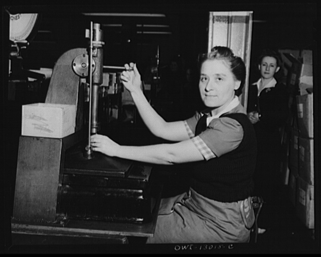 Detroit, Michigan. Assembly of Rolls Royce engines at the Packard Motor Car Company. Checking valve springs with an Arbor press for tension