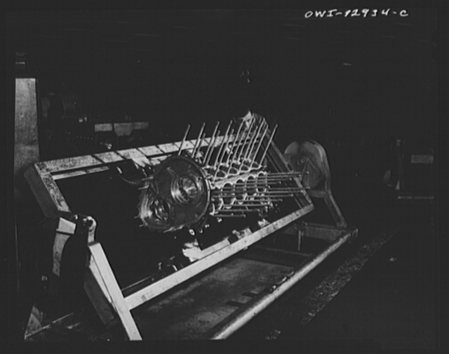Detroit, Michigan. Assembly of Rolls Royce engines at the Packard motor car company. Turning the crankcase over in a dolly before dropping the crankshaft