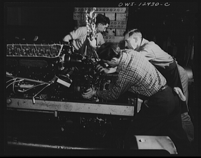 Detroit, Michigan. Assembly of Rolls Royce engines at the Packard motor car company. Assembling a super charger into an engine assembly