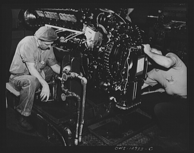 Detroit, Michigan. Assembly of Rolls Royce engines at the Packard motor car company. Connecting engine at a flush-in stand