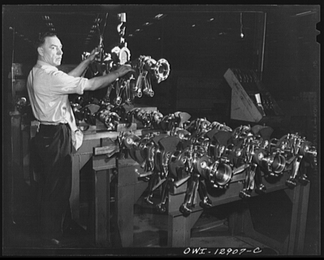 Detroit, Michigan. Assembly of Rolls Royce engines at the Packard motor car company. Group of connecting rods going into the crankshaft