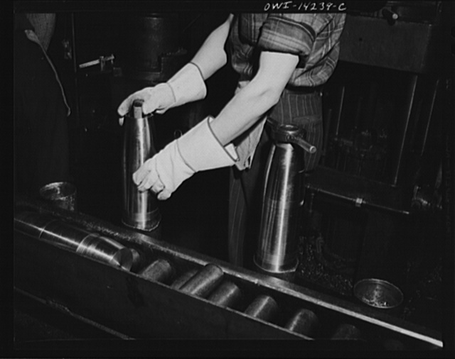 Detroit, Michigan. Steps in the manufacture of casings for 105 mm. shells in the Budd wheel plant. Process inspection of a shell: testing interior diameters and threads