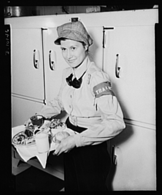 Emmy Banys, welder-trainee at General Motors' Eastern Aircraft Division in Linden, New Jersey, holds the forty-seven-cent Victory lunch which is served daily in the plant cafeteria. Including a small steak, two vegetables, salad, enriched breads, custard and a glass of milk, this type of nutritious lunch is providing war workers with the energy needed to maintain full production