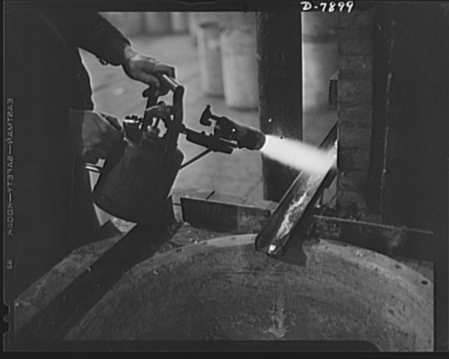 Empty collapsible tubes: a tin mine for war industry. Pure tin recovered from old tooth paste, shaving cream and other tubes is drawn off from a electric furnace in the Newark, New Jersey, plant of the Tin Salvage Institute. A blow torch is used to expedite the flow of tin until the molten metal heats the channel sufficiently to permit steady flow
