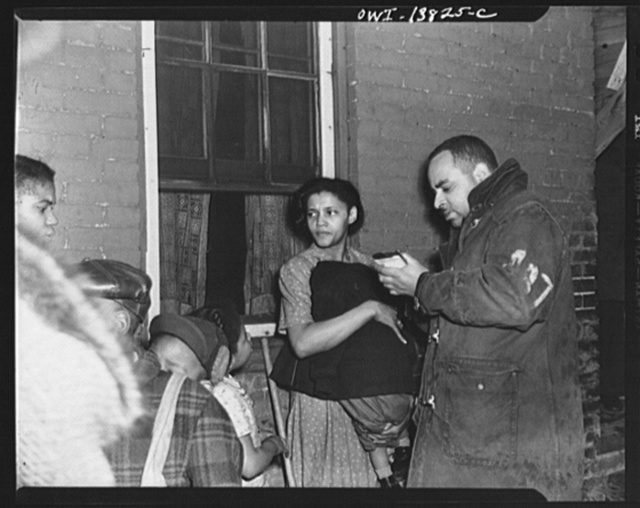 Firehouse Station No. 4. Washington, D.C. A mother holding a small child close to her body to protect him from the cold night. While the mother was away he had turned over a fuel-oil lamp whick set fire to the curtains. This fireman is taking notatations from the mother