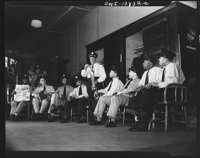 Firehouse Station No. 4. Washington, D.C. Captain J.B. Keyes yalking to some of the recently-appointed firemen about experiences at fires in the old days and showing one of the cups won by his company for the best-decorated floats in the city parades