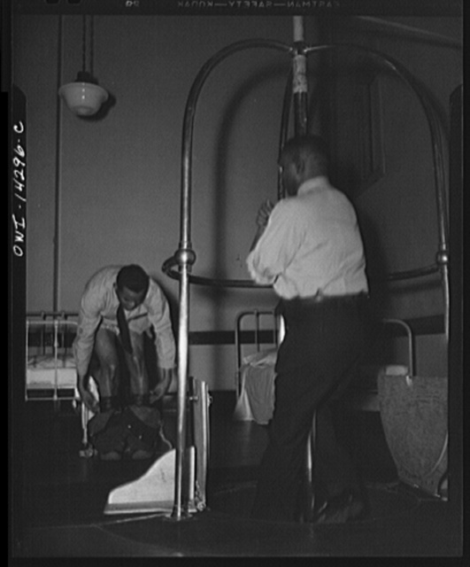 Firehouse station number four. Washington, D.C. A young fireman sleeps in his shirt and socks. When the alarm goes off he steps quickly into his boots that have pants attached complete with suspenders, adjusts them on the run, and slides down the pole to