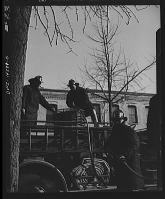 Firehouse station number four. Washington, D.C. Firemen retrieving a small hose after extinguishing a blaze. The young firemen in the foreground took his first ride