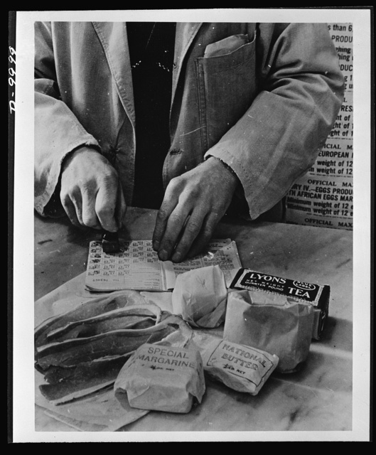 "Food in England. A shopkeeper cancels the coupons in a British housewife's ration book for the tea, sugar, cooking fats and bacon she is allowed for one week. Most foods in Britain are rationed and some brand names are given the designation ""National"""