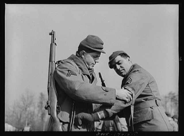 Fort Belvoir, Virginia. Corporal adjusting a rifle sling for Sergeant Biviano
