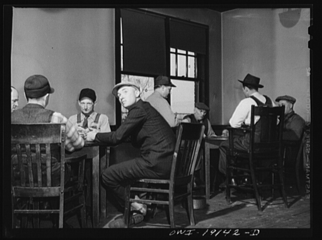 """Fort Madison, Iowa. Atchison, Topeka and Santa Fe Railroad men playing cards in the reading room. The company maintains """"reading rooms"""" at twenty division points which are houses containing recreation rooms, libraries, and most of them also have sleeping quarters"""