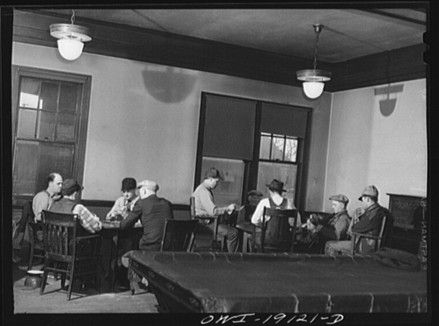 """Fort Madison, Iowa. Atchison, Topeka and Santa Fe Railroad men playing cards in the reading room. The company maintains """"reading rooms"""" at twenty division points which are houses containing recreation rooms, libraries and most of them also have sleeping quarters"""