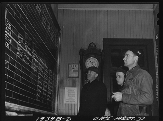 Fort Madison, Iowa. Atchison, Topeka and Santa Fe Railroad workers studying call board showing train crews to be called for various trains