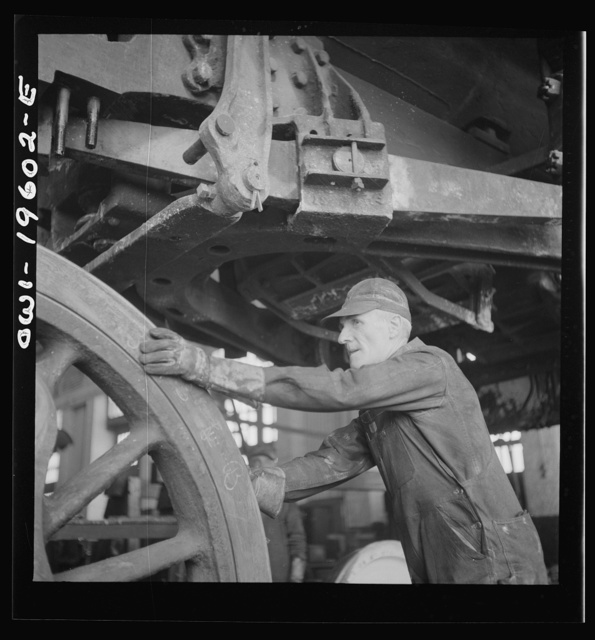 Fort Madison, Iowa. Edward E. Leonard pushing a driver wheel in place under an engine being wheeled at the Shopton locomotive shops of the Atchison, Topeka, and Santa Fe Railroad