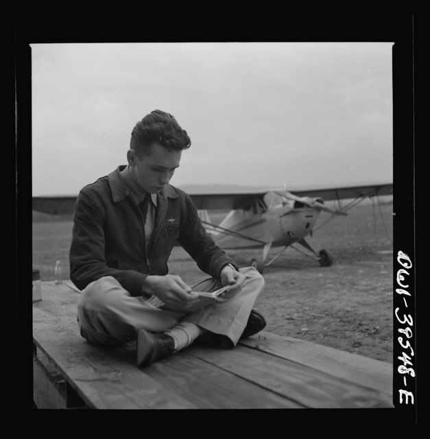 Frederick, Maryland. Walter Spangenberg, a student at Woodrow Wilson High School, studying his English lesson while waiting to fly at the Stevens Airport