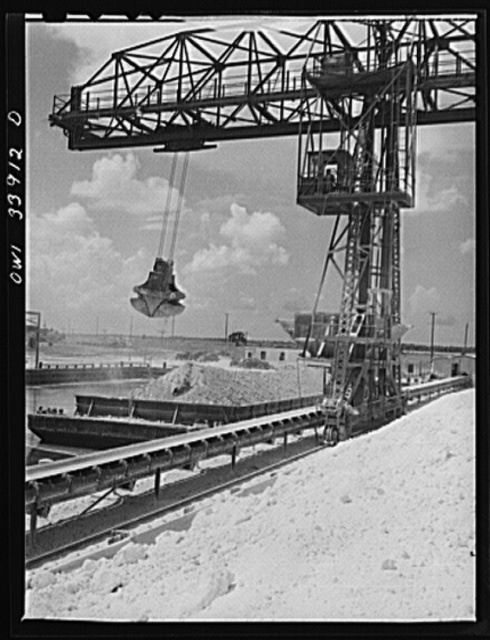 Freeport Sulphur Company, Port Sulphur, Louisiana. Unloading sulphur from a barge to storage vats