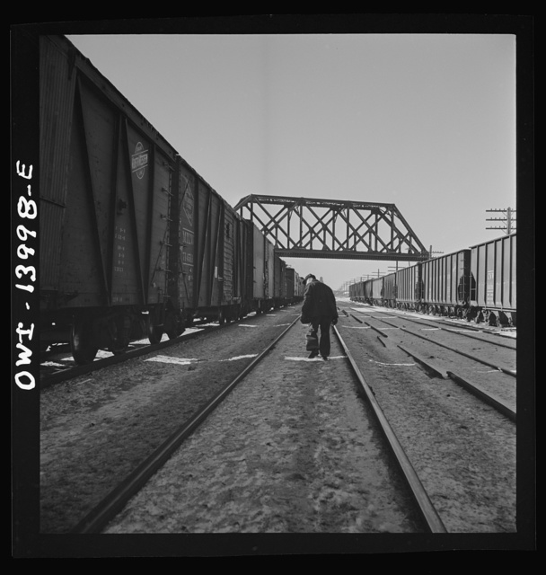 Freight train operations on the Chicago and Northwestern Railroad between Chicago and Clinton, Iowa. The train stops at DeKalb, Illinois for coal and water. The brakemen make an inspection of the train. Since their time is limited, they walk on the side opposite the wind so they smell any hot-boxes on the other side without having to walk both sides of the train
