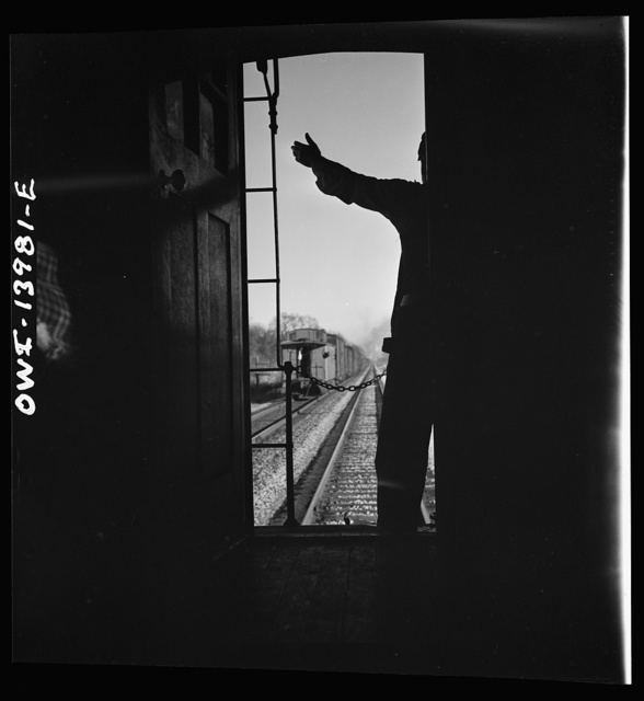 Freight train operations on the Chicago and Northwestern Railroad between Chicago and Clinton, Iowa. Every time a train is passed, the rear brakeman of each train steps out on the caboose platform, and if all is well, as in this case, gives the other brakeman the high sign