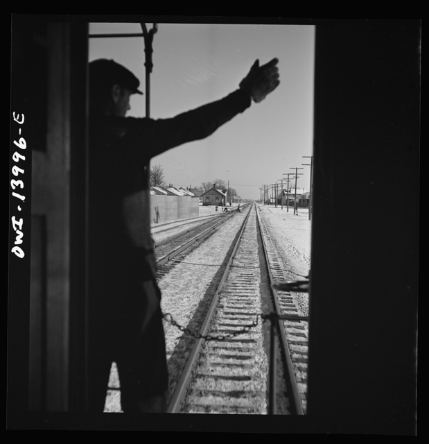Freight train operations on the Chicago and Northwestern Railroad between Chicago and Clinton, Iowa. As the train goes through a small town, the conductor exchanges high signs with a switch tender