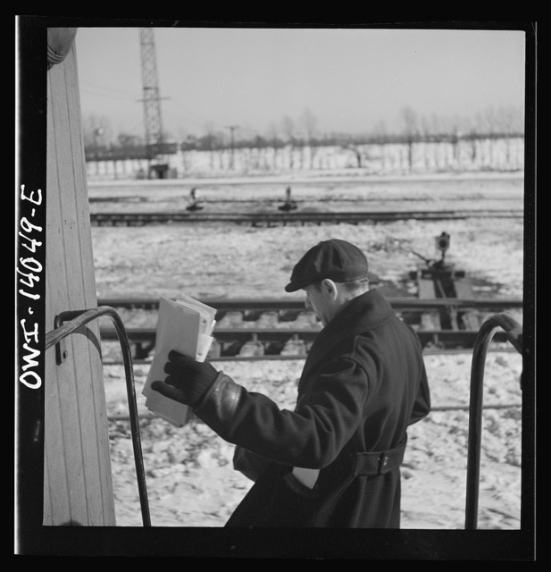 Freight trains operations on the Chicago and Northwestern Railroad between Chicago and Clinton, Iowa. Clutching his bills, Conductor Wolfsmith hops off the caboose as the train passes the yard office on its way into the receiving yard
