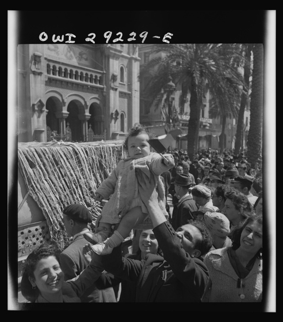 French citizens, in a frenzy of excitement, wave tricolors as Allied armies march into Tunis