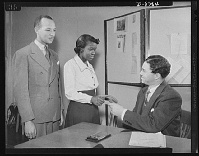 From National Youth Administration (NYA) to Washington navy yard. A full-fledged graduate from the National Youth Adminstration War Production and Training Center in Washington, D.C., Miss Juanita E. Gray, a former domestic worker, receives her certificate from J.P. Bond Jr., project manager, while E.R. Rodriguez, youth personnel officer, looks on. Miss Gray was referred immediately to the Washington navy yard