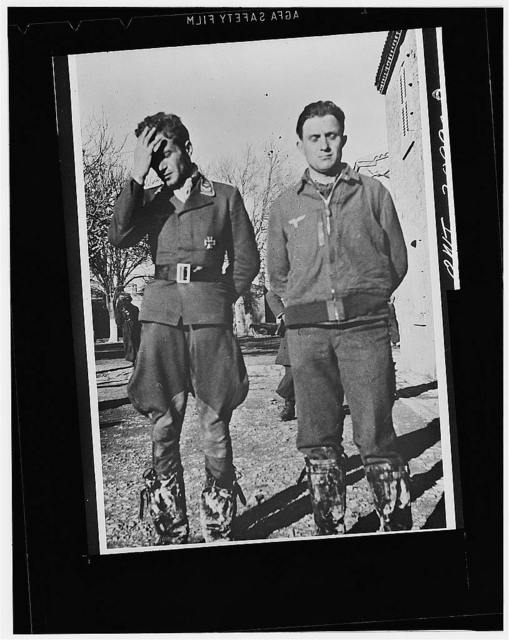 German airmen captured in northwest Africa after their bombing plane had been shot down by Allied fliers. The pilot, left, wears the Iron Cross. He and the crew member with him tried to escape after a crash landing