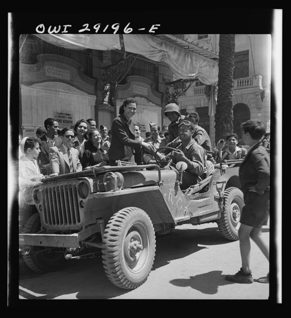 Girls climb on the Jeeps to greet American invading troops in the streets of Tunis