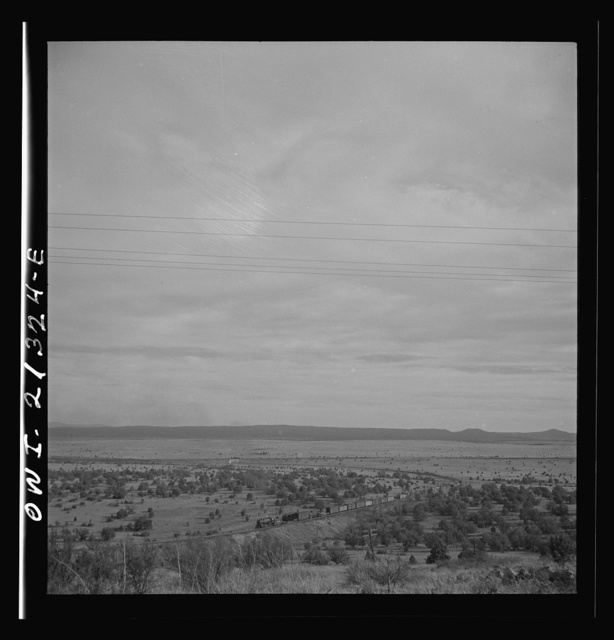 Gleed (vicinity), Arizona. A freight train going around a curve on the Atchison, Topeka and Santa Fe Railroad between Winslow and Seligman, Arizona