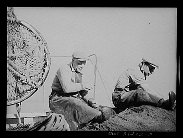 Gloucester, Massachusetts. Antionia Milietello and Vito Cannela of the fishing boat Alden repairing a seining net. These nets cost from seven to ten thousand dollars. Before the war one could be bought for three thousand dollars