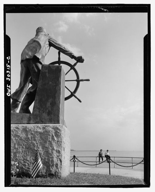 Gloucester, Massachusetts. The bronze fisherman, a memorial to men lost at sea. Each year flowers are placed at the feet of the fisherman and the roll of those lost at sea during the last year is slowly read, and an armfull of blossoms are strewn upon the water, to be carried by the ebb to unknown graves