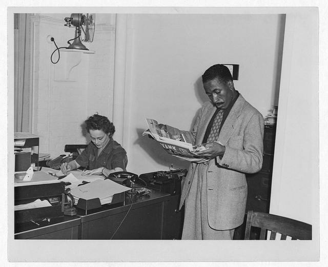 [Gordon Parks, Farm Security Administration/Office of War Information photographer, standing in office with Helen Wool seated at desk]