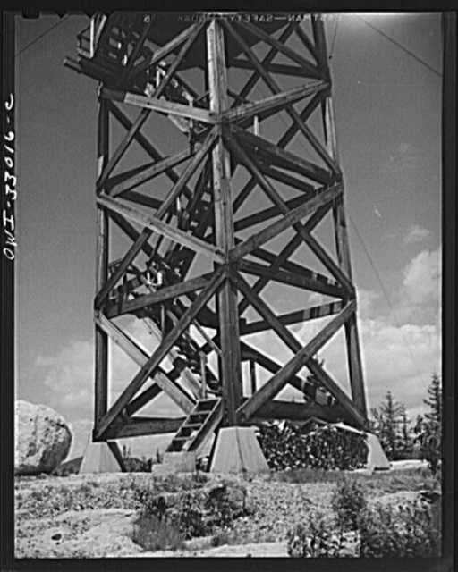 Gorham (vicinity), New Hampshire. Barbara Mortensen, a fire and airplane lookout on Pine Mountain, mounts fifty-six steps to reach the fire tower