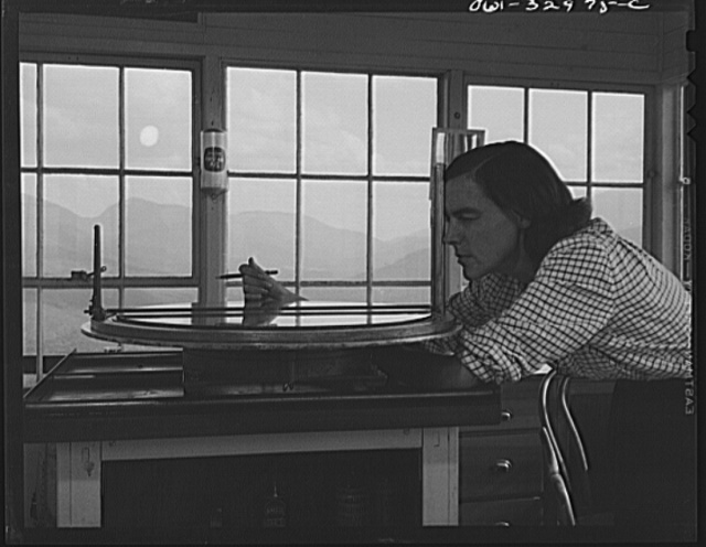 Gorham (vicinity), New Hampshire. Barbara Mortensen, a fire and airplane lookout on Pine Mountain, sighting through the fire finder which accurately locates fires on topographical maps