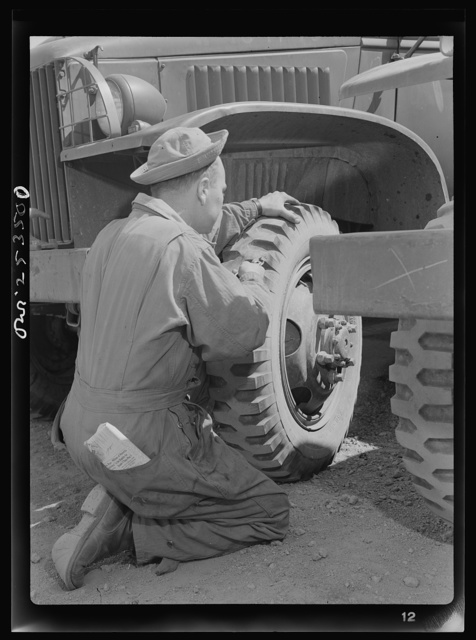 Holabird ordnance depot, Baltimore, Maryland. A soldier removing a tack from a United States Army truck tire. Constant fire inspection is required of all drivers at the depot