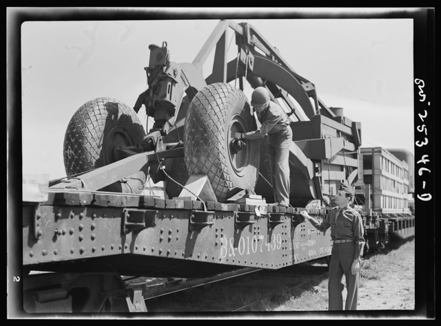 Holabird ordnance depot, Baltimore, Maryland. An officer checking the air pressure of the giant tires on LeTourneau road scrapers which are being sent overseas. Pressure must be ten pounds above normal load to keep tires in best condition during the journey