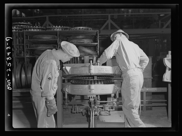 """Holabird ordnance depot, Baltimore, Maryland. In the recapping shop, after the application of camelback, the tire is placed in a mold and is """"cured"""" for about one hour and forty-five minutes. Here soldiers are removing it from the mold; as soon as it has cooled it is ready for use"""