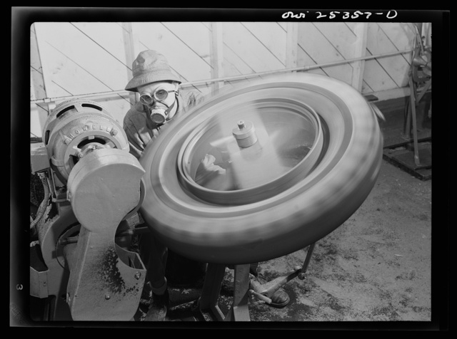 Holabird ordnance depot, Baltimore, Maryland. The buffing room in the recapping shop. Before being recapped, tires must be buffed. The rasp buffs rubber off. This rubber is afterwards collected for salvage
