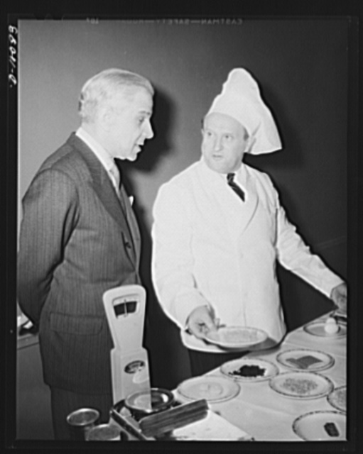 Honorable Cimon P. Diamantopoulos, the ambassador of Greece to the United States, examines food which had first been dehydrated, then rehydrated, for serving at a luncheon in observance of the second anniversary of lend-lease, held March 11, 1943, at Hotel Statler, Washington, D.C.