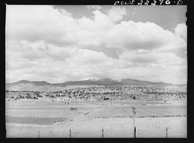 Indian farms and houses near Laguna, New Mexico enroute to Gallup on the Atchison, Topeka, and Santa Fe Railroad. In the background is Mount Taylor