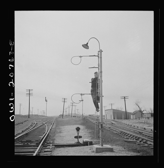Isleta, New Mexico. Mr. Young standing on hoops with messages to be picked up by passing train on the Atchison, Topeka and Santa Fe Railroad