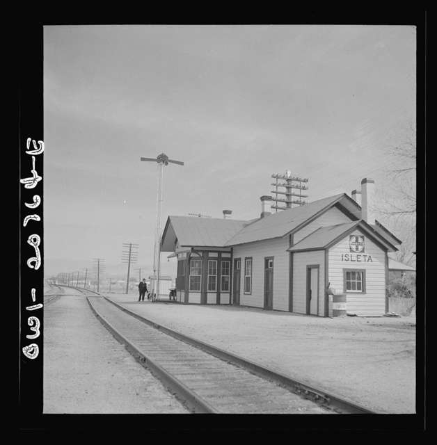 "Isleta, New Mexico. The depot. Horizontal arms on pole indicate a ""red beard,"" that is a message is to be picked up by the train crew of the Atchison, Topeka and Santa Fe Railroad"