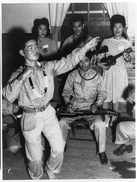 [Japanese American soldiers of the 442nd Combat Team at dance, Camp Shelby, Mississippi, with Japanese American girls from Jerome and Rohwer Relocation Center in Arkansas: Private Harry Hamada doing hula dance and his guitar-ukulele orchestra]